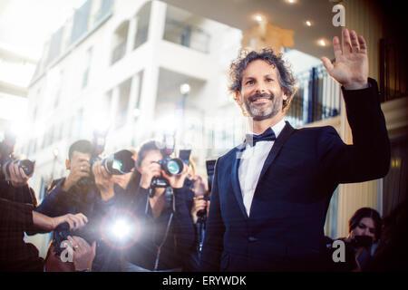 Saludando a los fotógrafos paparazzi de celebridades en el evento