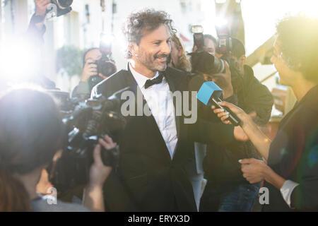 Celebridad entrevistada y fotografiada por paparazzi fotógrafos en evento de alfombra roja