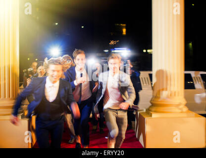 Entusiasta de las celebridades que llegan y se ejecuta desde paparazzi fotógrafos en evento de alfombra roja