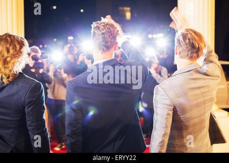 Celebridades ondeando y fotografiada por paparazzi fotógrafos en evento de alfombra roja