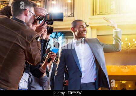 Celebrity ondeando y fotografiada por fotógrafos paparazzi