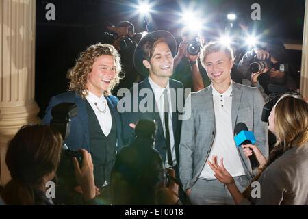 Celebridades sonriente entrevistada y fotografiada por fotógrafos paparazzi en el evento