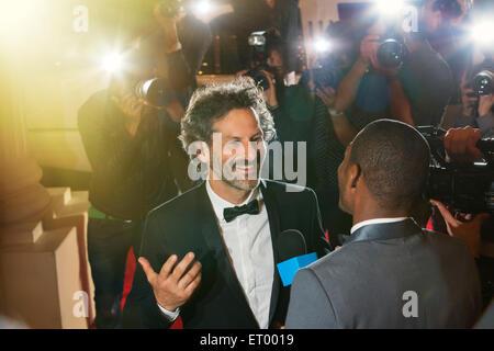 Celebridad entrevistada y fotografiada por fotógrafos paparazzi en el evento