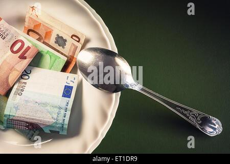 Varios billetes en la placa blanca con una cuchara en un lado, composición conceptual acerca del dinero. Foto de stock