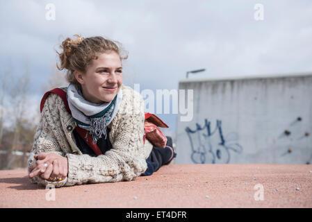 Retrato de un joven tumbado en la rotonda y sonriente Baviera Munich Alemania