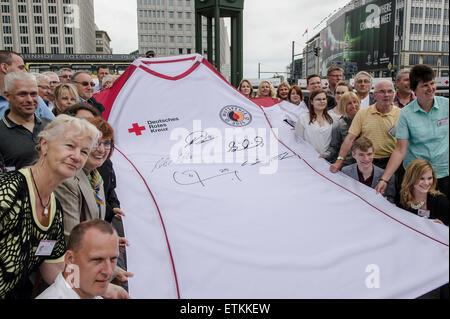 Berlín, Alemania. El 14 de junio de 2015. Los donantes de sangre posar delante de un enorme jersey de la Cruz Roja Alemana durante una campaña de donación de sangre de la organización marcando el Día Mundial del Donante de Sangre en Berlín, Alemania, el 14 de junio de 2015. Foto: Paul ZINKEN/dpa/Alamy Live News