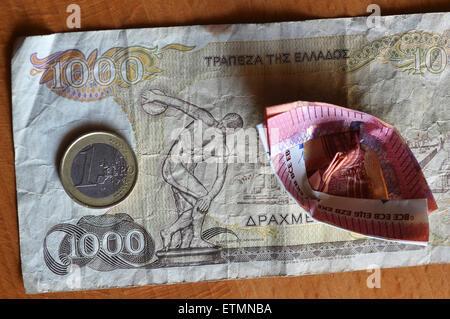 Berlín, Alemania. El 14 de junio de 2015. Ilustración - una moneda en euros y a 10 euros el proyecto de ley que ha sido doblada en un barco yace sobre un dracma griego 1000 Bill en Berlín, Alemania, el 14 de junio de 2015. Foto: Jens Kalaene/dpa/Alamy Live News