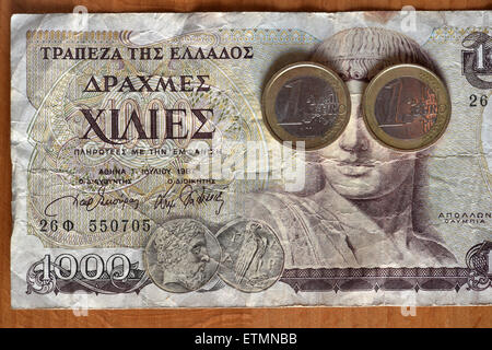 Berlín, Alemania. El 14 de junio de 2015. Ilustración - dos monedas de euro cubrir los ojos del dios griego Apolo en 1000 dracma griego bill en Berlín, Alemania, el 14 de junio de 2015. Foto: Jens Kalaene/dpa/Alamy Live News