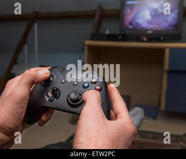 Teen in den jugando con controlador de juegos en TV Foto de stock