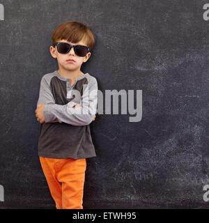 Retrato de niño inteligente con gafas de sol de pie con sus manos contra la pizarra con copyspace plegada.