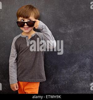 Retrato de un niñito en gafas de sol mirar lejos en el espacio de copia. Cool boy mirando por encima de sus gafas de sol contra la pizarra.