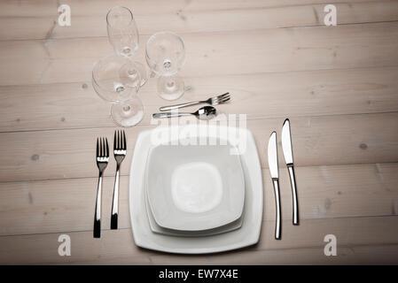 Conjunto de mesa con platos, cubiertos y vasos en la mesa de madera