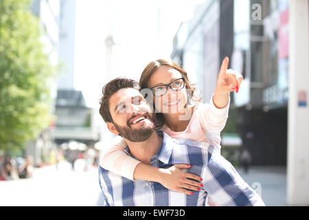 Mujer alegre apuntando hacia fuera mientras disfruta piggyback paseo sobre el hombre en la ciudad