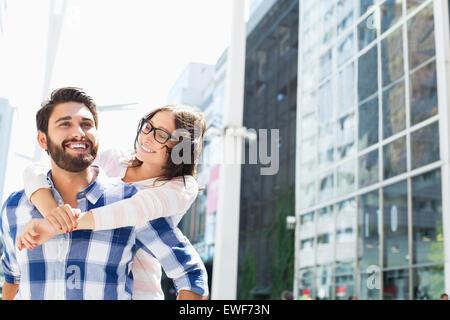 Hombre feliz viaje piggyback dando a la mujer en la ciudad