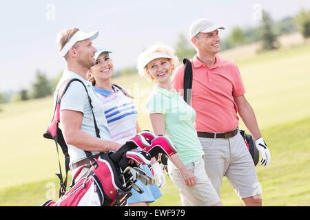 Feliz amigos caminando por el campo de golf Foto de stock