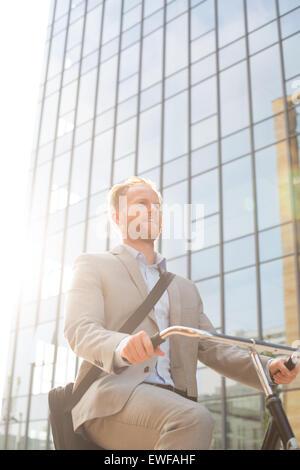 Ángulo de visión baja del empresario montando bicicleta fuera del edificio de oficinas en día soleado