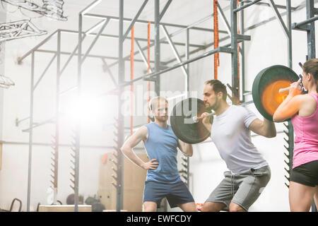 La gente ayudando al hombre en el levantamiento barbell en crossfit gimnasio