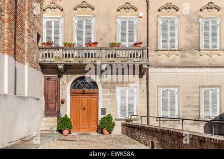 Fachada de la casa típica italiana con balcón y puerta de madera en la ciudad de La Morra en el Piamonte, Norte Foto de stock