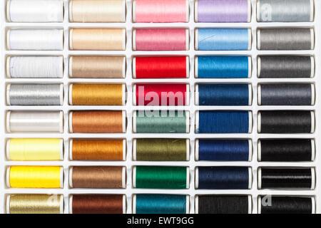 Muchos colores diferentes hilos de costura dispuestos en una paleta.