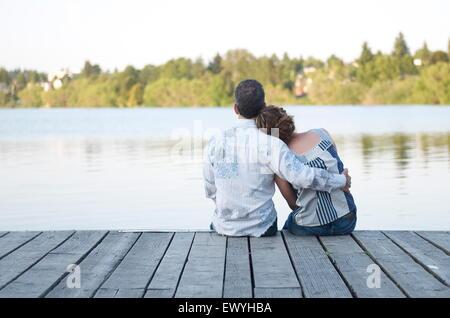 Vista trasera de una pareja sentada en un muelle de madera abrazando