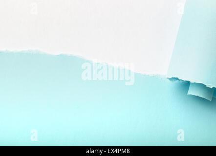 Desgarro en un pedazo de papel azul revelando fondo blanco debajo