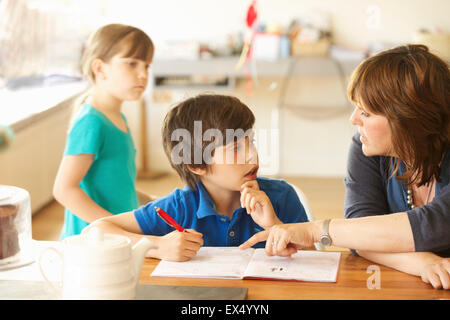 Madre e hijo haciendo los deberes en la Mesa de la cocina, hija en segundo plano.