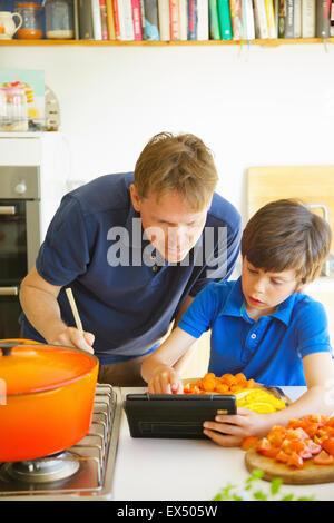Padre e Hijo cocinar usando tableta digital en la cocina Foto de stock