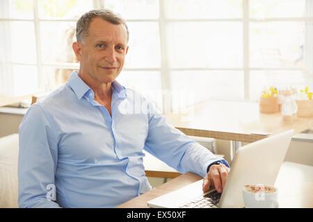 Hombre maduro con laptop en Cafe