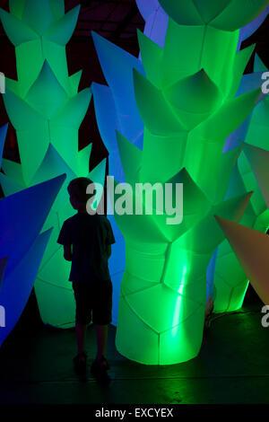 Boy a explorar el bosque de árboles de neón inflados, expresando tanto la curiosidad y la timidez a través de su postura
