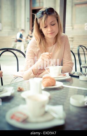 Hermosa mujer rubia de desayunar en el bar de la ciudad