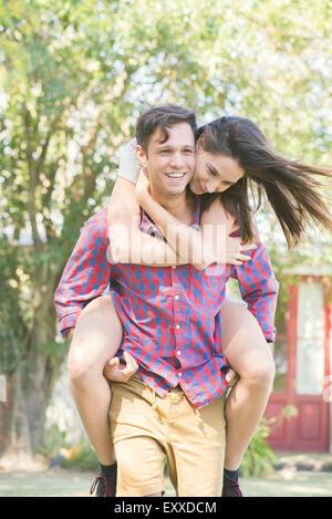 La pareja al aire libre, hombre mujer dando un paseo piggyback