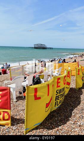 Brighton Reino Unido Sábado 18 de julio de 2015 - Un socorrista vigila como Brighton Beach está repleta esta tarde como la gente disfruta del buen tiempo