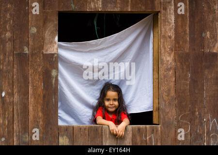 Cute Little Girl en la ventana de su casa de madera sonriendo ante la cámara en el Castillo, Nicaragua