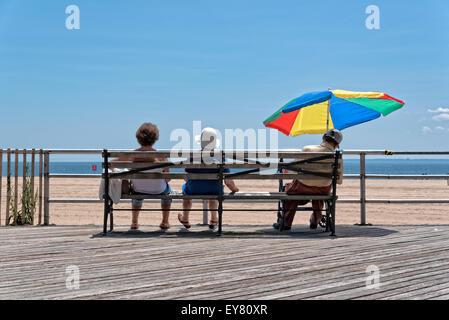 Tres ancianos (dos mujeres y un hombre) sentado en un banco. El hombre está bajo una sombrilla y aparentemente tomando una siesta.