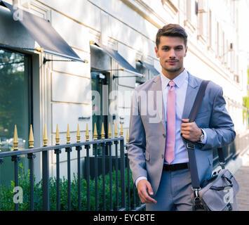 Retrato de un guapo joven empresario de caminar en la ciudad