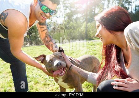 Joven pareja besándose en el parque del perro