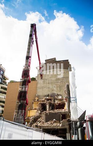 Grúa y digger trabajando en la demolición de edificios en las ciudades