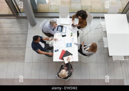 Vista aérea del equipo empresarial tras reunión en la mesa de conferencias
