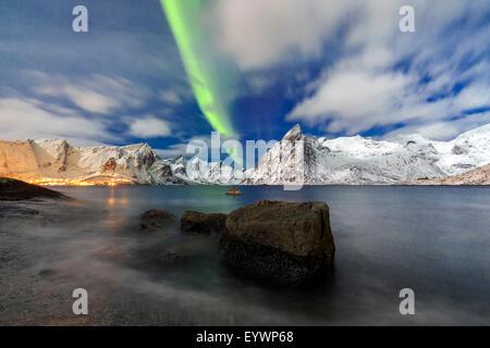 Las luces del norte (aurora borealis) iluminan Hamnoy village y picos nevados, Islas Lofoten, Ártico, en Noruega, Escandinavia