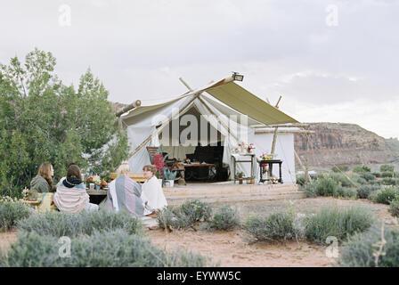 Grupo de mujeres con amigos, disfrutando de una comida al aire libre en un desierto por una gran carpa.