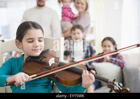 Chica caucásica a tocar el violín en la sala de estar
