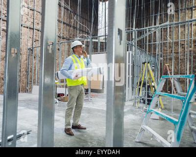 Trabajador caucásico llevar planos en sitio en construcción