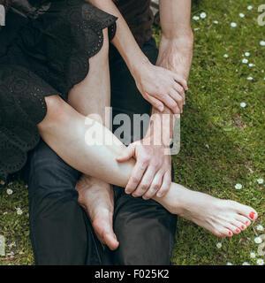 Primer plano de un hombre maduro, manteniendo los pies de una mujer madura en su mano