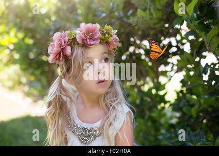 Niña mirando una mariposa, California, EE.UU