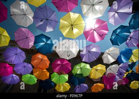 Coloridas sombrillas flotante llenan el cielo sobre la rue Jean Jaures, Arles, Bouches-du-Rhône, departamento de Provence, Francia