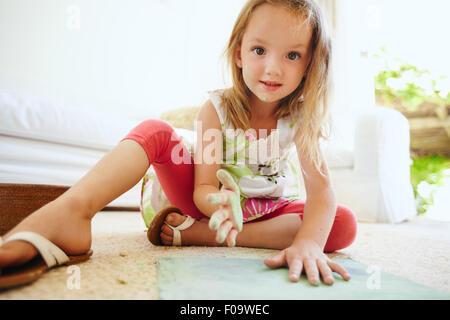 Retrato de hermosa Little Schoolgirl colorear una foto. Chica manos pintadas con tiza de color verde mirando a la cámara.