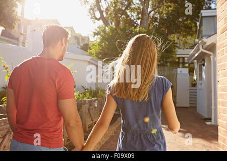 Vista trasera de la joven pareja a su casa caminando juntos. Pareja en patio teniendo caminar en un día soleado.