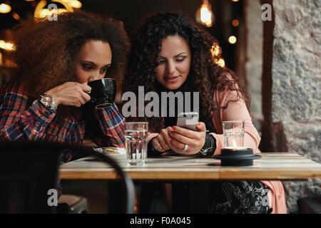 Jóvenes amigos sentado en un café mirando a un smartphone. Una mujer bebiendo café y otro holding, teléfono móvil Foto de stock