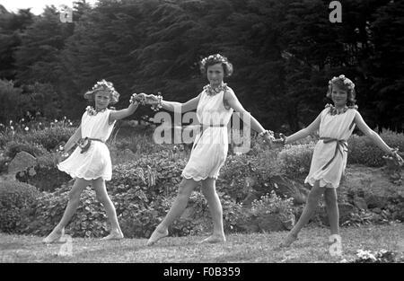Dos chicas adolescentes con su madre bailando en un jardín luciendo vestidos con collares y pulseras de flores Foto de stock