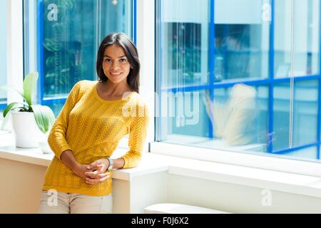Sonriente atractiva empresaria de pie cerca de la ventana en la oficina y mirando a la cámara
